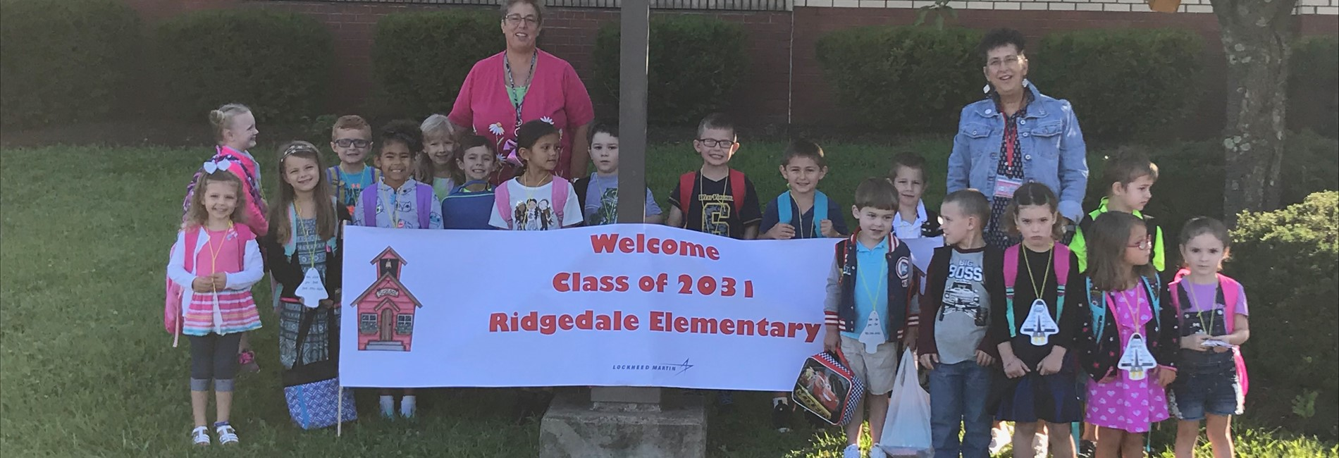 "Pic""  kindergarten students in front of welcome banner"